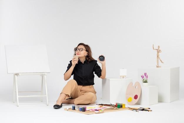 Jovem mulher sentada de frente na sala com tintas e cavalete sobre fundo branco