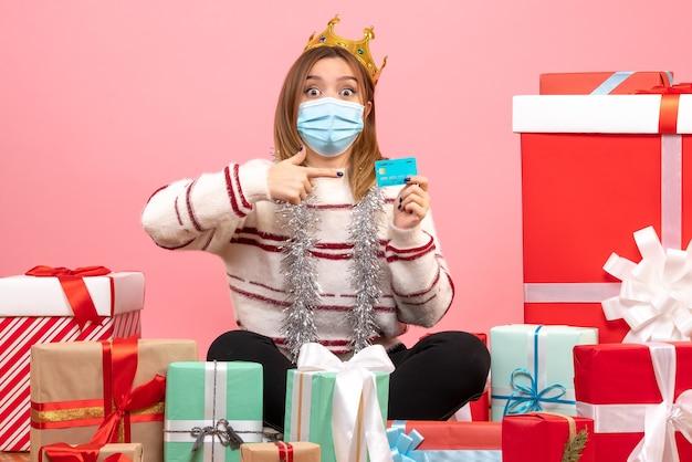 Jovem mulher sentada de frente para o natal apresenta com cartão do banco