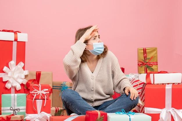 Jovem mulher sentada de frente para o natal apresenta-se com máscara