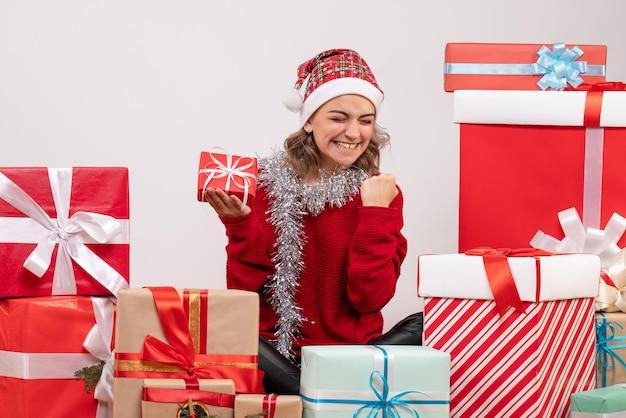 Jovem mulher sentada de frente para os presentes de natal e regozijando-se