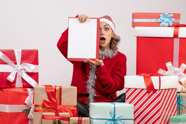 Jovem mulher sentada de frente para os presentes de natal