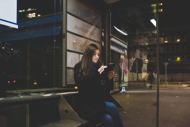 Jovem mulher sentada de ônibus usando smartphone