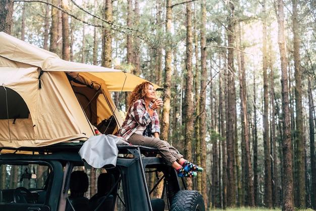 Jovem mulher sentada do lado de fora da barraca no telhado do carro e bebendo café na floresta. mulher relaxando e olhando para a floresta coberta de árvores. mulher feliz admirando a natureza enquanto acampa no topo do carro