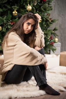 Jovem mulher sentada e posando perto de árvore de natal.