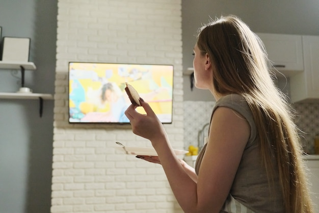 Jovem mulher sentada em casa assistindo tv e comendo