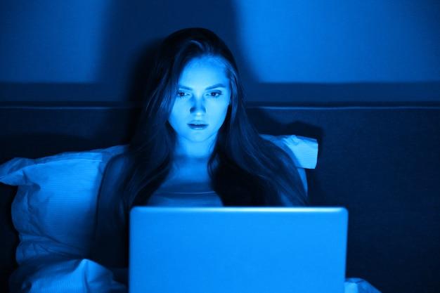 Jovem mulher sentada em casa na cama à noite com um laptop