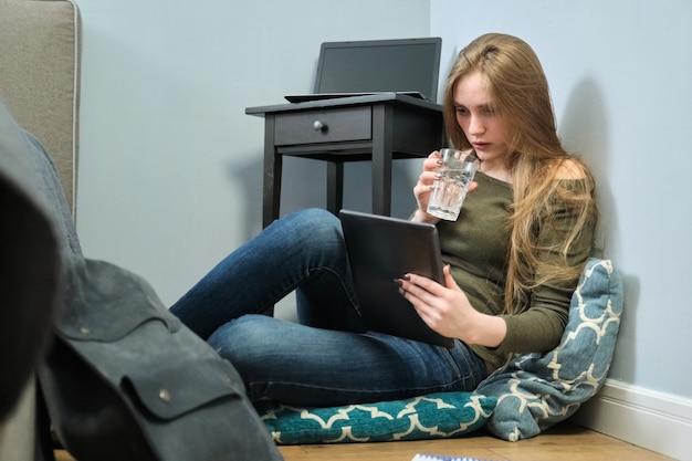 Jovem mulher sentada em casa no chão com tablet digital e copo de água. menina estuda, lê, descansa usando a internet