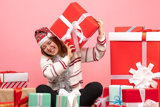 Jovem mulher sentada em frente aos presentes de natal Foto gratuita