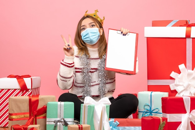 Jovem mulher sentada em frente aos presentes de natal