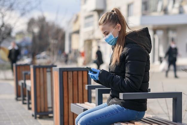 Jovem mulher sentada em um banco de rua com máscara médica e roupas pretas