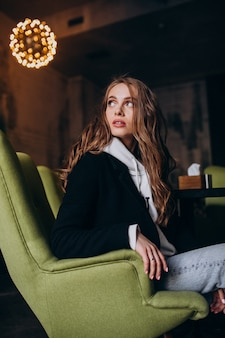 Jovem mulher sentada em uma cadeira dentro de um café