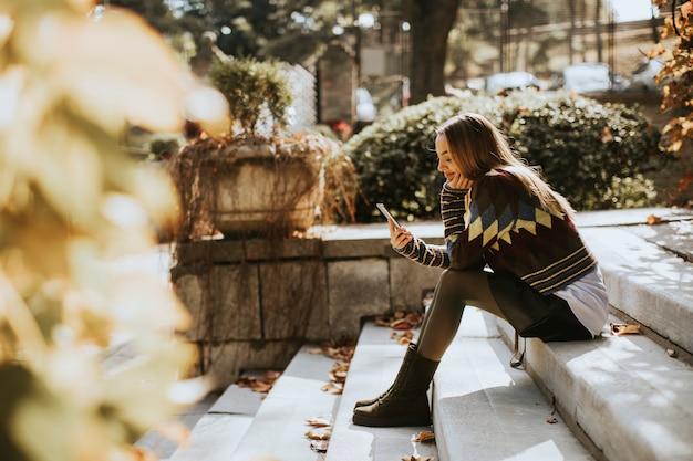 Jovem mulher sentada em uma escada com telefone celular no parque outono