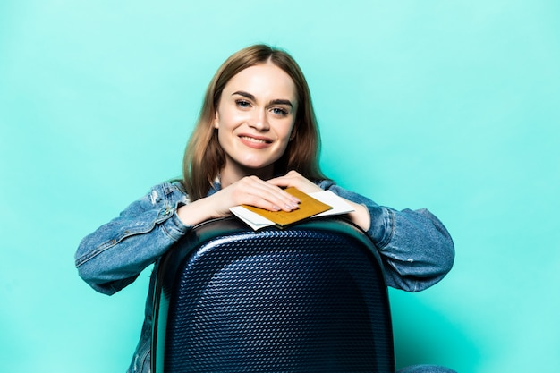 Jovem mulher sentada em uma mala vermelha com bilhetes nas mãos dela isolado na parede verde