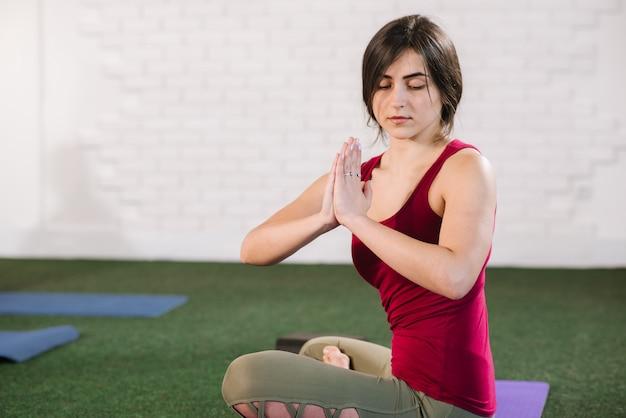 Jovem mulher sentada em uma pose de lotos inddors