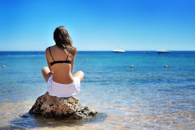 Jovem mulher sentada na areia e olhando para o mar.