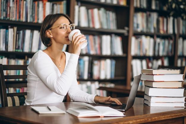 Jovem mulher sentada na biblioteca usando livros e computador