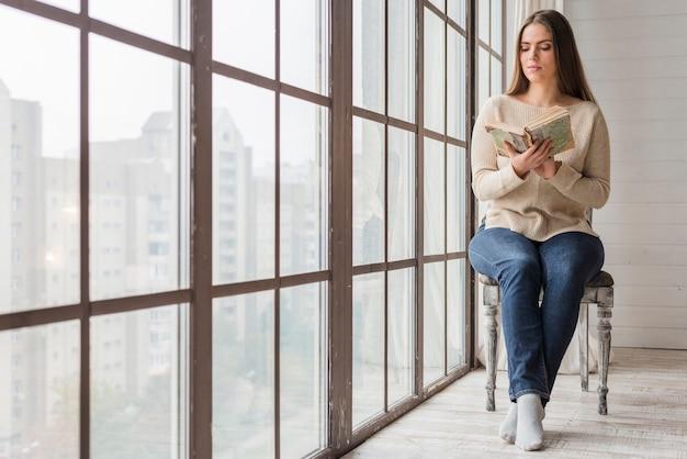 Jovem mulher sentada na cadeira de madeira perto da janela lendo o livro