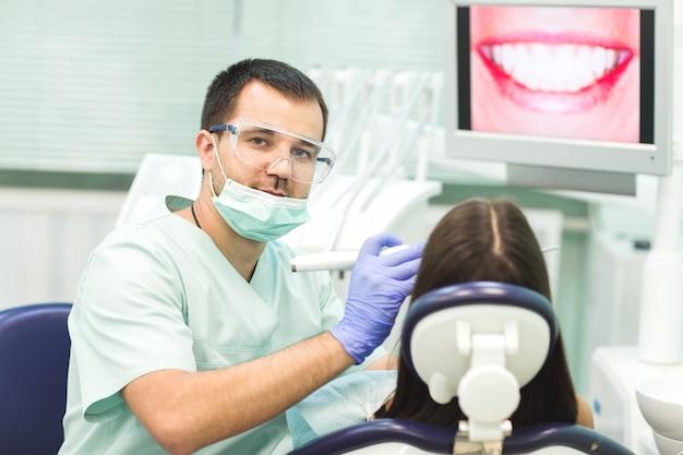 Jovem mulher sentada na cadeira do dentista com a boca aberta no consultório do dentista enquanto faz o exame.