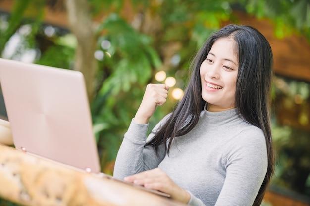 Jovem mulher sentada na cafeteria na mesa de madeira, bebendo café e usando o laptop.