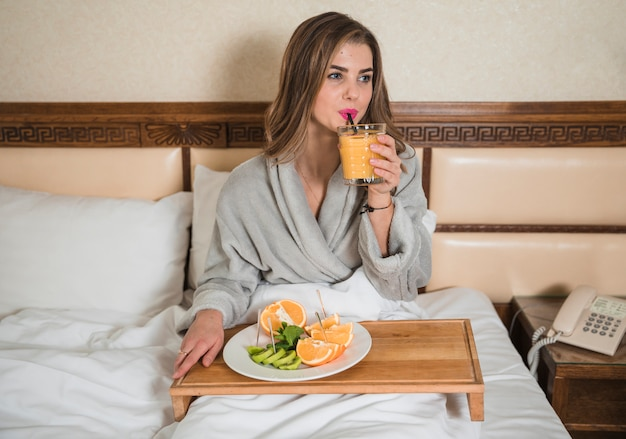 Jovem mulher sentada na cama, bebendo o copo de suco