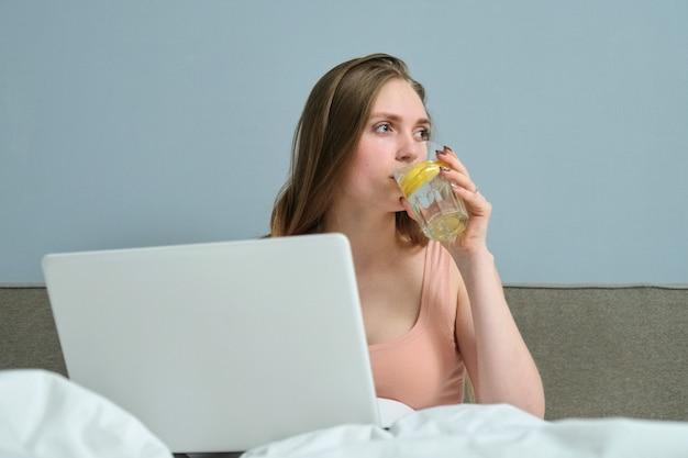 Jovem mulher sentada na cama com o computador portátil e água potável com limão