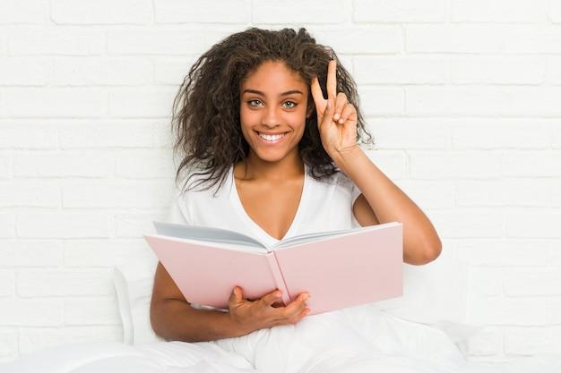 Jovem mulher sentada na cama estudando mostrando sinal de vitória e sorrindo amplamente