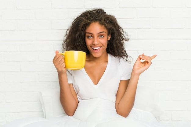 Jovem mulher sentada na cama segurando uma caneca de café sorrindo alegremente apontando com o dedo indicador fora