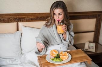 Jovem mulher sentada na cama tomando café da manhã nutritivo, olhando para o telefone inteligente