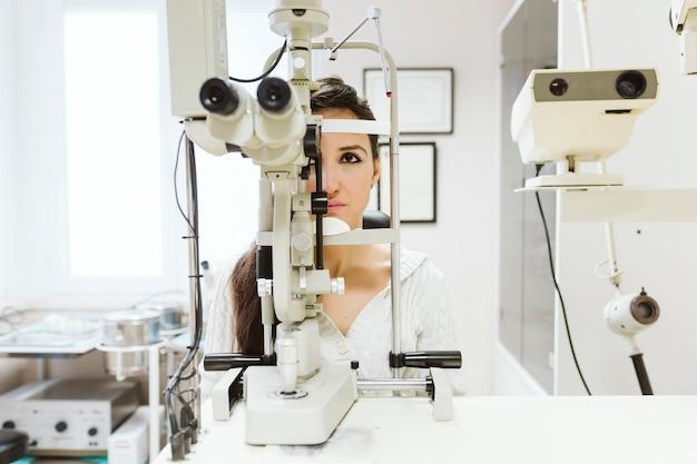 Jovem mulher sentada na clínica de oftalmologista para obter os olhos examinados por um profissional.