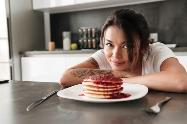 Jovem mulher sentada na cozinha a sorrir