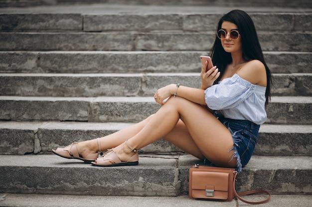 Jovem mulher sentada na escada a falar ao telefone