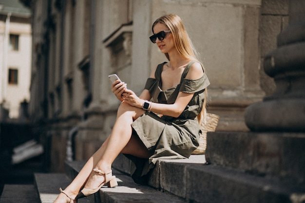 Jovem mulher sentada na escada e falando ao telefone