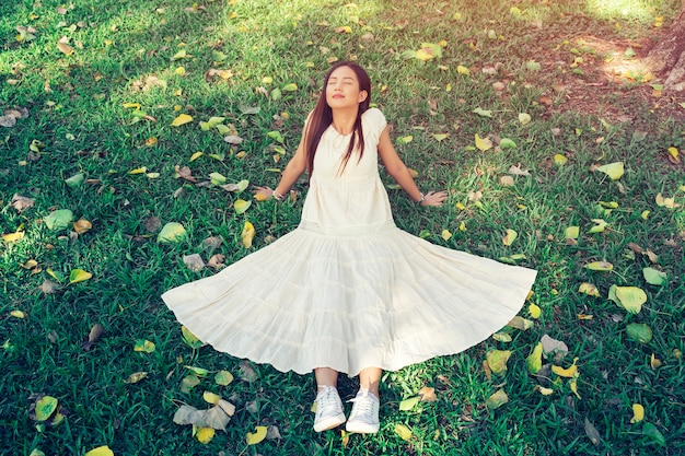 Jovem mulher sentada na grama verde com relaxar e sorrir