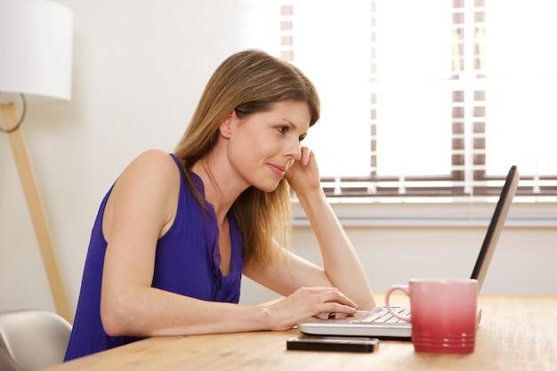 Jovem mulher sentada na mesa olhando para a tela do laptop