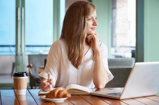Jovem mulher sentada na mesa, segurando a caneta e olhando para a janela