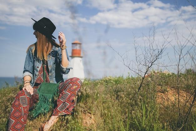 Jovem mulher sentada na natureza, farol, roupa boêmia, jaqueta jeans, chapéu preto, sorridente, feliz, verão, acessórios elegantes
