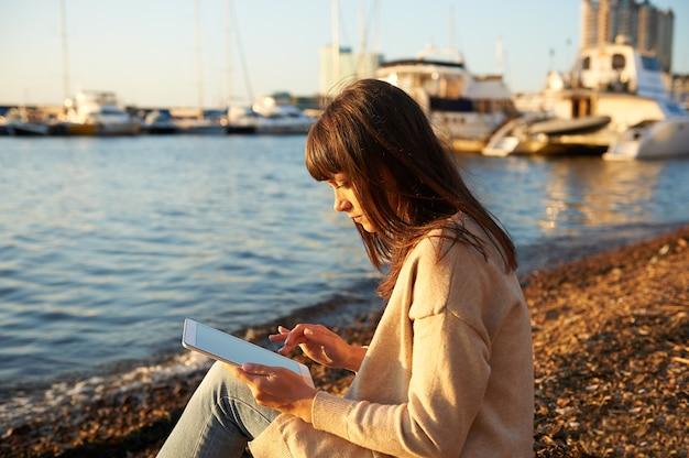 Jovem mulher sentada na praia, ao pôr do sol, lendo no tablet