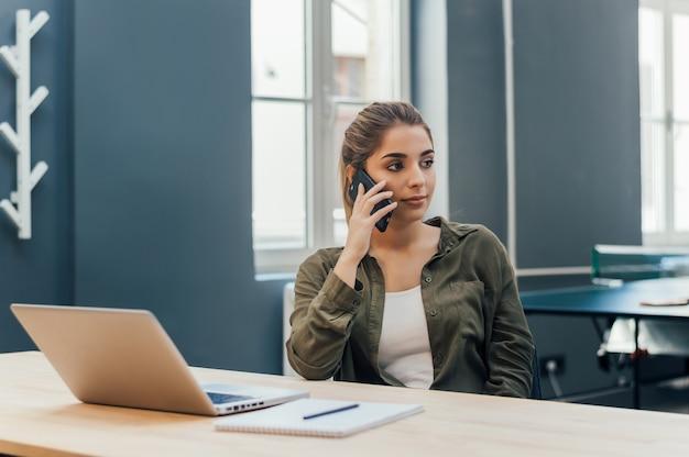 Jovem mulher sentada na sala com interior moderno e falando no celular.