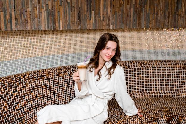 Jovem mulher sentada na sauna e beber café ..