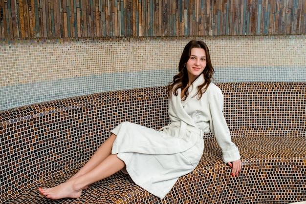 Jovem mulher sentada na sauna e sorrindo
