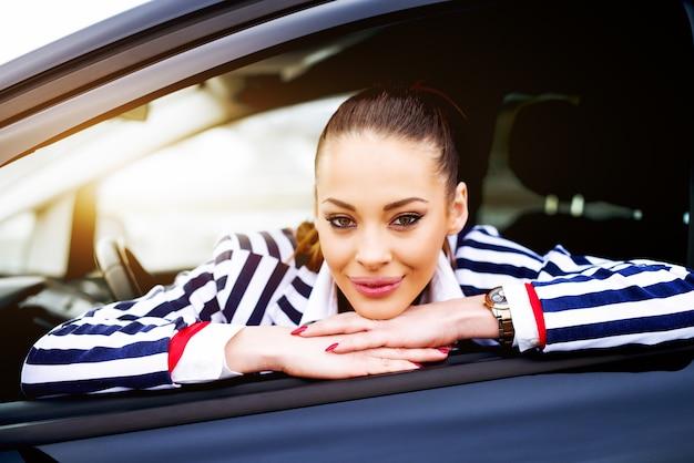 Jovem mulher sentada no banco do motorista e olhando pela janela.