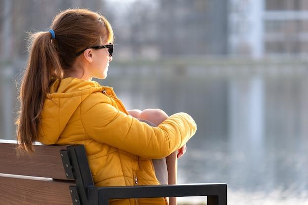 Jovem mulher sentada no banco do parque relaxante num dia quente de primavera.