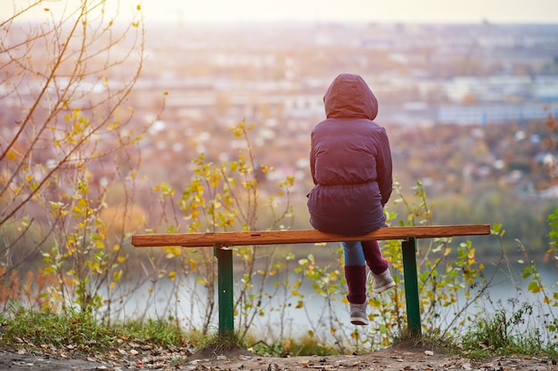 Jovem mulher sentada no banco no outono parque da cidade e olhando a paisagem urbana, vista traseira.