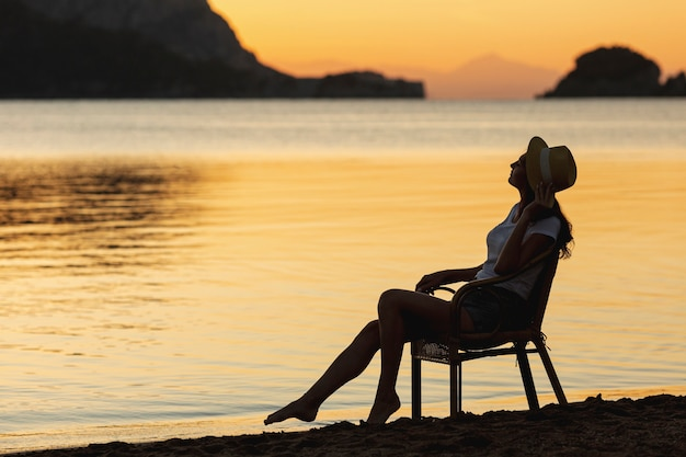 Jovem mulher sentada no banco por do sol na margem de um lago