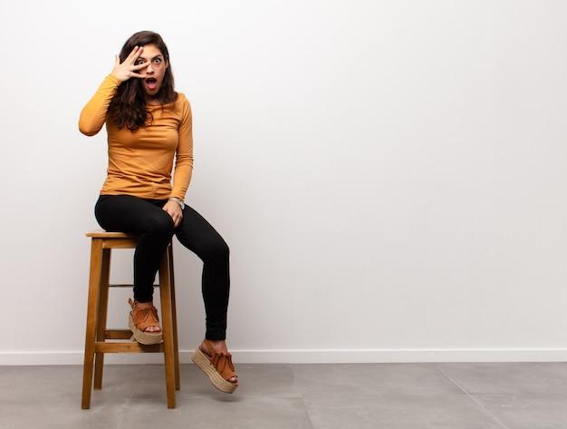 Jovem mulher sentada no banquinho com expressão chocada