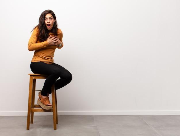Jovem mulher sentada no banquinho com expressão de surpresa