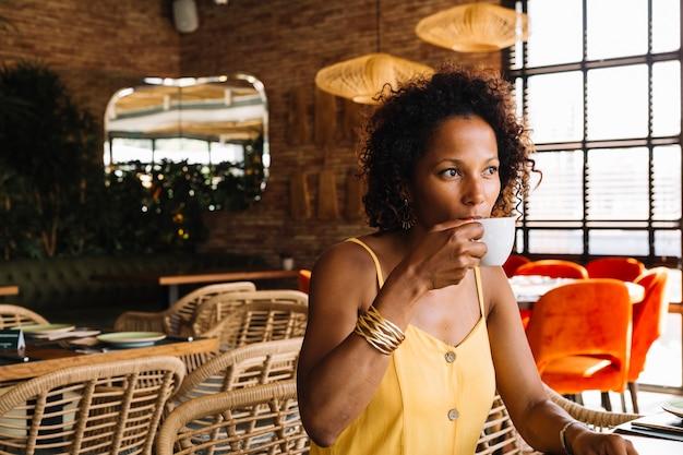 Jovem mulher sentada no café a beber café