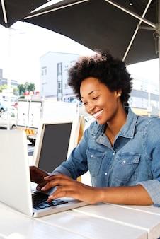 Jovem mulher sentada no café ao ar livre com laptop
