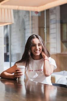 Jovem mulher sentada no café segurando uma xícara de café descartável na mesa