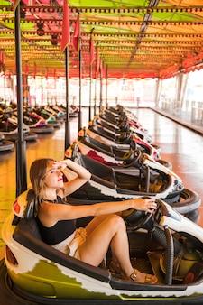Jovem mulher sentada no carro pára-choques, protegendo os olhos no parque de diversões